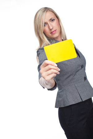 watchfulness: Stylish frowning woman holding up a yellow card to the camera showing that a flagrant foul has been committed, isolated on white Stock Photo