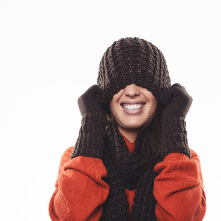 Playful woman hiding under a knitted brown winter hat pulling it down over her eyes with a laughing smile, isolated on white photo