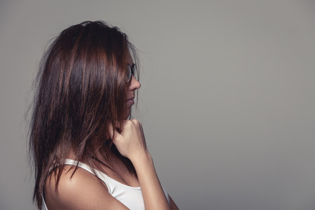 downhearted: Woman with untidy long brown hair standing sideways with the hair hiding her face, on grey with copyspace