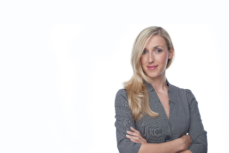 confiding: Confident stylish blond businesswoman standing looking at the camera with her arms crossed, on white with copyspace Stock Photo
