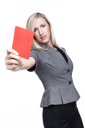 dismiss: Stern young woman or referee in a stylish grey top showing a red card to send a player off the field or out of the game, isolated on white