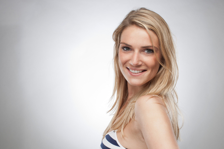 charismatic: Close up Smiling Young Woman with Blond Hair in Trendy Outfit, Wearing Sleeveless Stripe Tops. Looking at the Camera. Isolated on Gray Background.