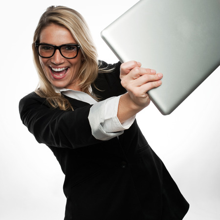 exuberant: Exuberant excited young blond businesswoman in glasses laughing and cheering as she brandishes her laptop towards the camera Stock Photo