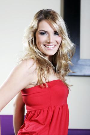 red tube: Close up Felice giovane donna con capelli biondi in rosso sexy superiore del tubo. Guardando la fotocamera.