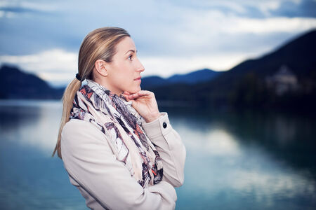 sombre: Sombre young woman in stylish autumn fashion standing thinking with her hand to her chin and a melancholy expression, side view in front of a tranquil mountain lake Stock Photo