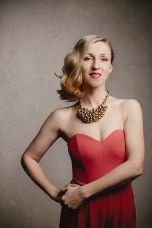 'evening wear': Elegant blond woman in stylish evening wear wearing a strapless red dress and feature necklace standing smiling at the camera with her hand on her hip, grey background Stock Photo