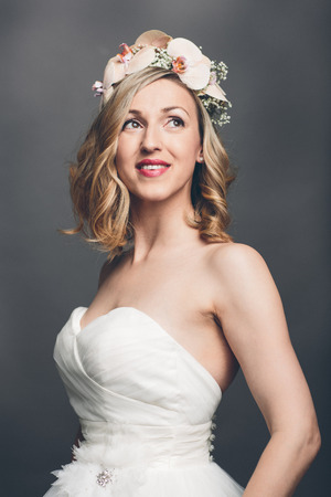 introspective: Elegant pretty bride with flowers in her hair wearing a strapless white bridal dress standing looking meditatively up into the air with a tender smile, upper body over grey Stock Photo