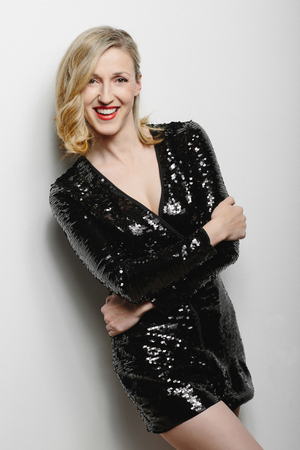 chic woman: Chic attractive glamorous blond woman in a stylish black cocktail dress standing laughing at the camera with her arms folded across her body, frontal three-quarter view Stock Photo