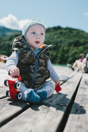 absorbed: Adorable baby boy sitting outdoors on a wooden deck playing with a plastic toy and sitting up watching someone off screen with a cute absorbed expression