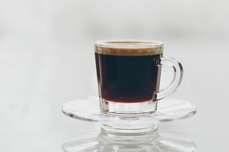 addictive drinking: Cup of delicious freshly brewed full roast frothy black espresso coffee served in a glass mug and saucer on a reflective grey background