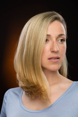 inscrutable: Close up Pretty Blond Young Woman in Casual Shirt, Looking Into Distance Seriously. Captured in Studio with a Brown Gradient Background. Stock Photo