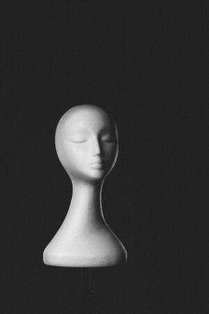 ladies bust: Minimalist artistic modern bust of a serene woman with closed eyes and a long graceful neck over a black background with copyspace
