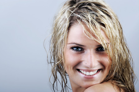 attractive charismatic: Close up Happy Attractive Young Woman with Wet Blond Hair, Looking at the Camera with Toothy Smile Against Gray Background with Copy Space.
