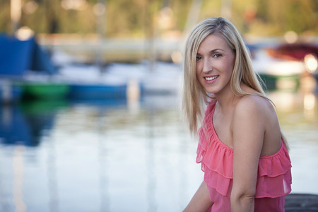 copysapce: Attractive Blond Girl in Sexy Pink Dress, Sitting on the Lakeside and Smiling at the Camera Against Blurry Lake Water with Resting Boats.