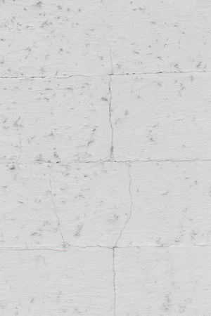 discolored: Grunge wall background texture with cracked discolored white paint and damp spots in a full frame view