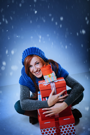 clasping: Happy attractive redhead woman sitting cross-legged on the ground clasping a pile of colorful red Christmas gift boxes under falling winter snow with copy space for your seasonal holiday greeting Stock Photo