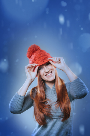 vivacious: Vivacious laughing young redhead woman in a festive red hat standing outdoors in falling snow smiling merrily at the camera, copy space for a Christmas or seasonal greeting Stock Photo