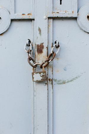 chaining: Close up view of old, locked and chained painted white gate with bits of rust showing through surface