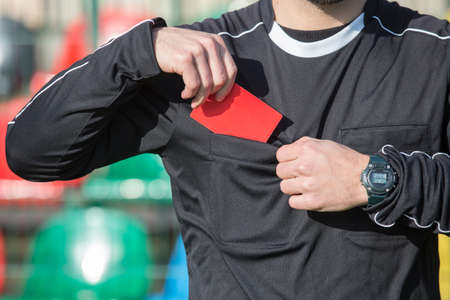 Football referee showing the red card.