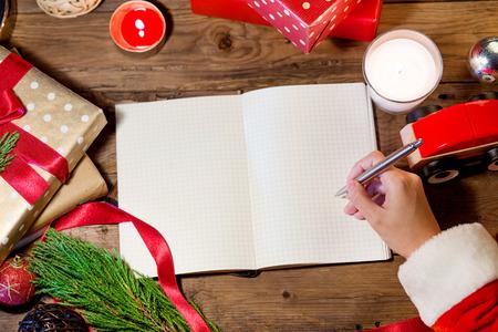 santa hand: Santa hand writing on christmas book.