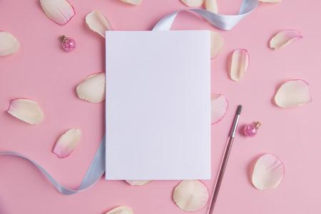 파스텔 배경에 분홍색 꽃잎과 흰 종이입니다. 스톡 콘텐츠