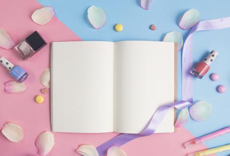 파스텔 배경에 분홍색 꽃잎 가진 오픈 책.