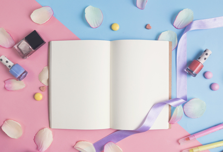 Open book with pink petals on pastel background.