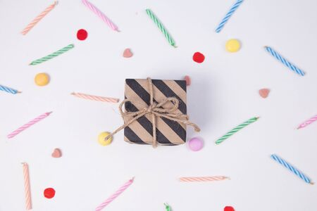 Giftbox with candlesand candy for birthday on pink background.