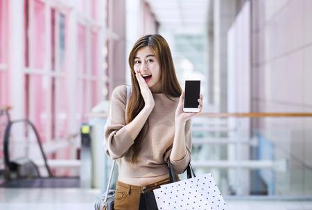 Aziatische meisjes met boodschappentassen met smartphone