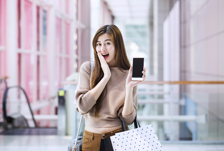 Asian girls with shopping bags using smartphone Banque d'images