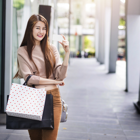 Beautiful asian woman with shopping bags and a card Stock Photo