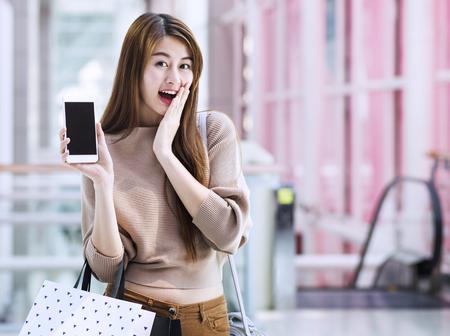 スマート フォンを使用したショッピング バッグとアジアの女の子