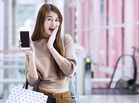 Las niñas asiáticas con bolsas de la compra utilizando el teléfono inteligente Foto de archivo - 79662121