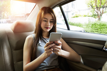 Young asian woman use smartphone in car