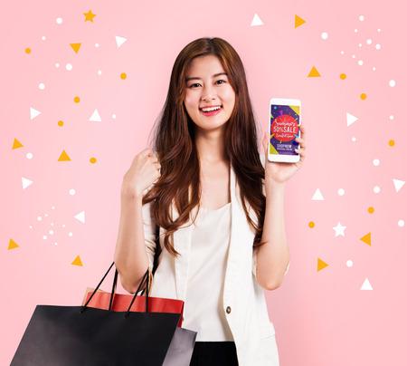 Leuk meisje met papier boodschappentas en mobiele telefoon op pastel achtergrond Stockfoto