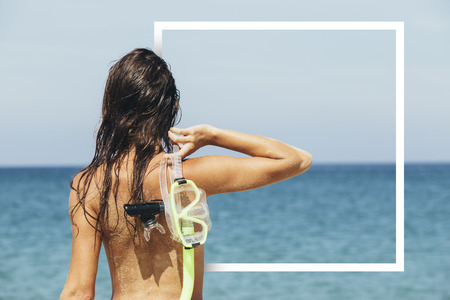 A sexy woman with scuba mask in frame on the beach Stock Photo