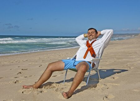 a business man relaxing and catching sun on the beach Stock Photo