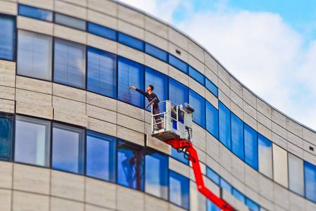 Moscow, Russia, April 17, 2019: Cleaning by the worker-climber of the glass modern facade of the buildin