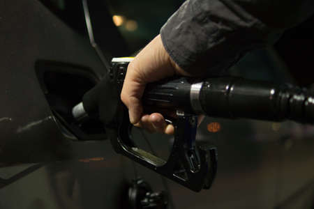 White car refueling at gas station with green fuel nozzle. Stock Photo