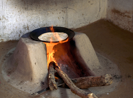 a typical wood fired oven or chulha used to cook food in rural india with a chapati on it 스톡 콘텐츠