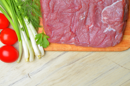 Fresh raw piece of meat lies on the kitchen blackboard next to onions, parsley and tomatoes on a wooden table, top view photo