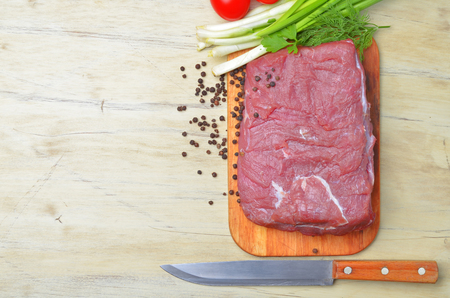 Fresh raw piece of meat lies on the kitchen blackboard next to onions, parsley and tomatoes and a knife with a wooden handle on a wooden table, top view photo