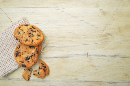 Golden brown, chocolate chip cookies over wooden table.