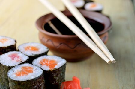 sauce bowl: Sushi chopsticks over soy sauce bowl, salmon rollsi and marinated ginger on rustic wooden table. Background  with copy space.