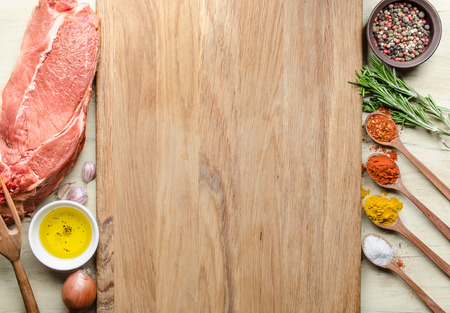 Food background with raw meat steaks and seasoning. Concept of ingredients for cooking steak, top view of the raw meat, chopping board in the middle, virgin Olive Oil, onion, garlic, pepper, rosemary, Caen pepper, turmeric, salt, ground red paprika in woo