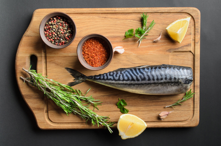 ingredients for baking scomber fillets, include raw mackerel, lemon, garlic, pepper, rosemary, from above on wooden cutting board. Rustic style.