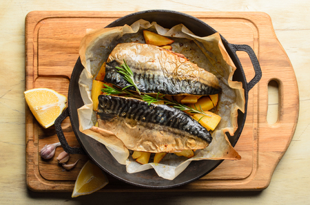 Baked fish mackerel with baked potato in a pan, rosemary, lemon and spice on a cutting board on a wooden background