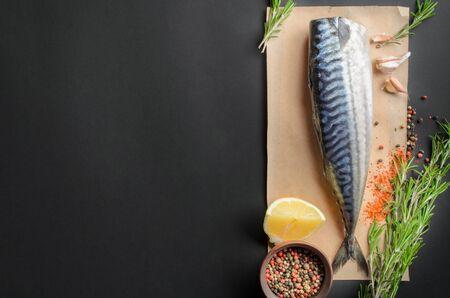 ingredients for baking scomber fillets, include raw mackerel, lemon, garlic, pepper, rosemary on a black background.