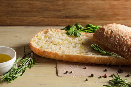 watered: Sliced bread ciabatta watered with extra virgin olive oil with herbs  on wooden background Stock Photo