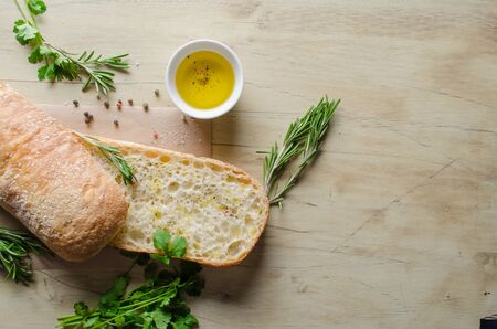 watered: Sliced bread ciabatta watered with extra virgin olive oil with herbs  on wooden background. View from above.